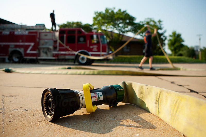 Firehouse: Firemen Resetting Fire Hose on Truck by Sean Locke for Stocksy United