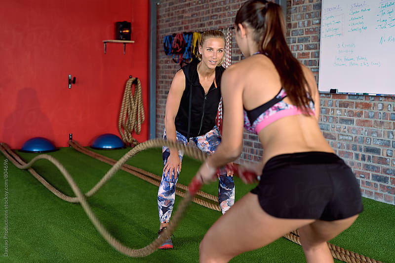 Fitness trainer explaining proper rope technique  by Daxiao Productions for Stocksy United