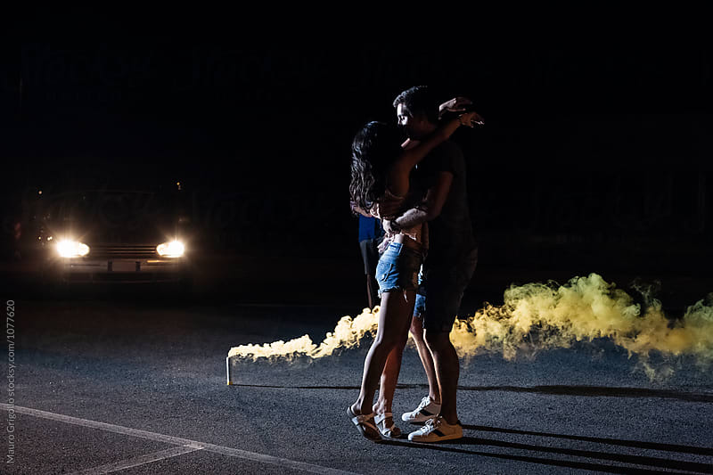 Couple flirting outdoor during a street party at night by Mauro Grigollo for Stocksy United