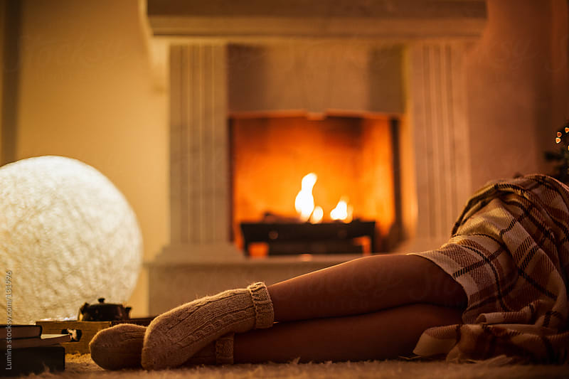 Woman Lying by the Fireplace by Lumina for Stocksy United