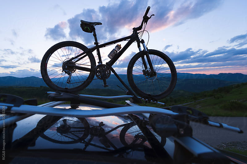 Mountain bike on car roof rack in nature by RG&B Images for Stocksy United