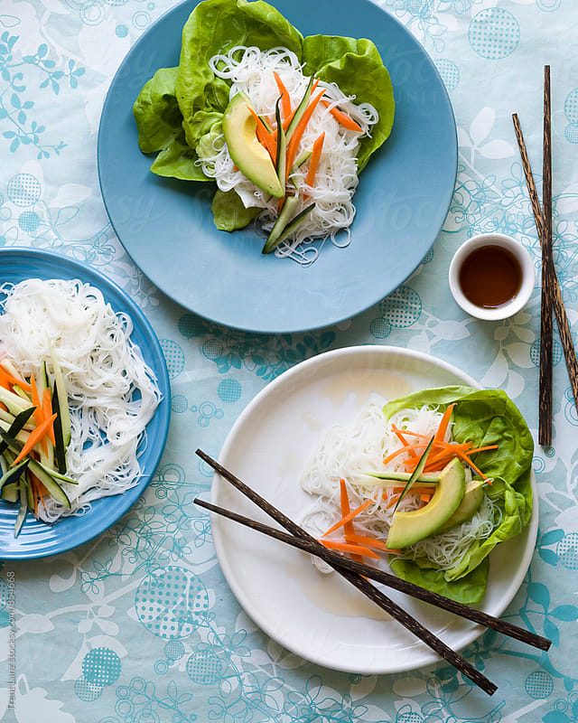 Thai food:spring roll rice noodles, soy sauce, salad, carrot, avocado, zucchini by Trent Lanz for Stocksy United