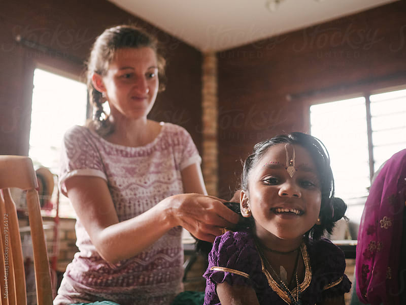 Happy adopted Indian girl smiling while her mum combs her hair by Martin Matej for Stocksy United
