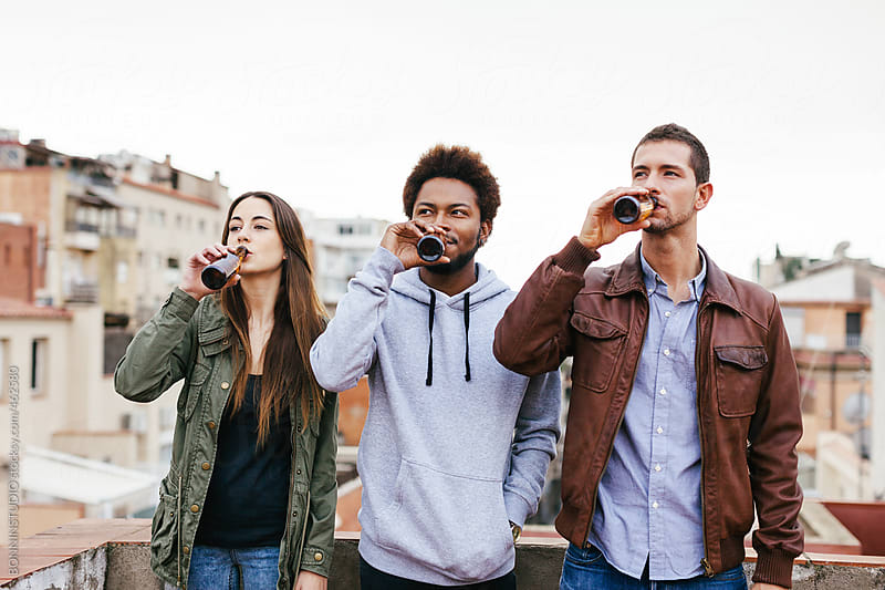 Group of friends having fun and drinking some beer on a rooftop. by BONNINSTUDIO for Stocksy United