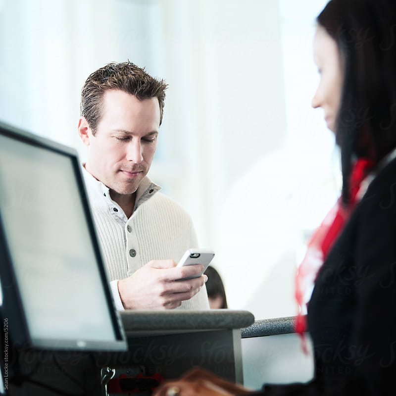 Airport: Main Checking Smart Phone For Ticket Information by Sean Locke for Stocksy United