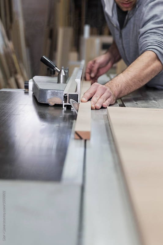 Closeup of carpenter trimming wood on a radial table saw by Lior + Lone for Stocksy United