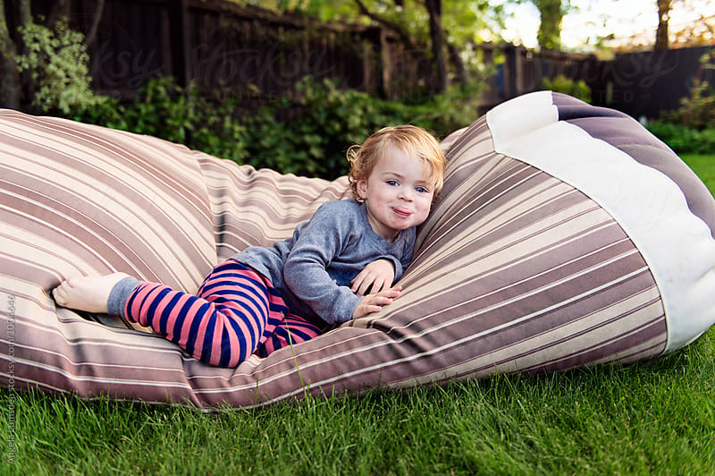 Cheeky toddler in pajamas poking out his tongue while lying on a beanbag by Angela Lumsden for Stocksy United