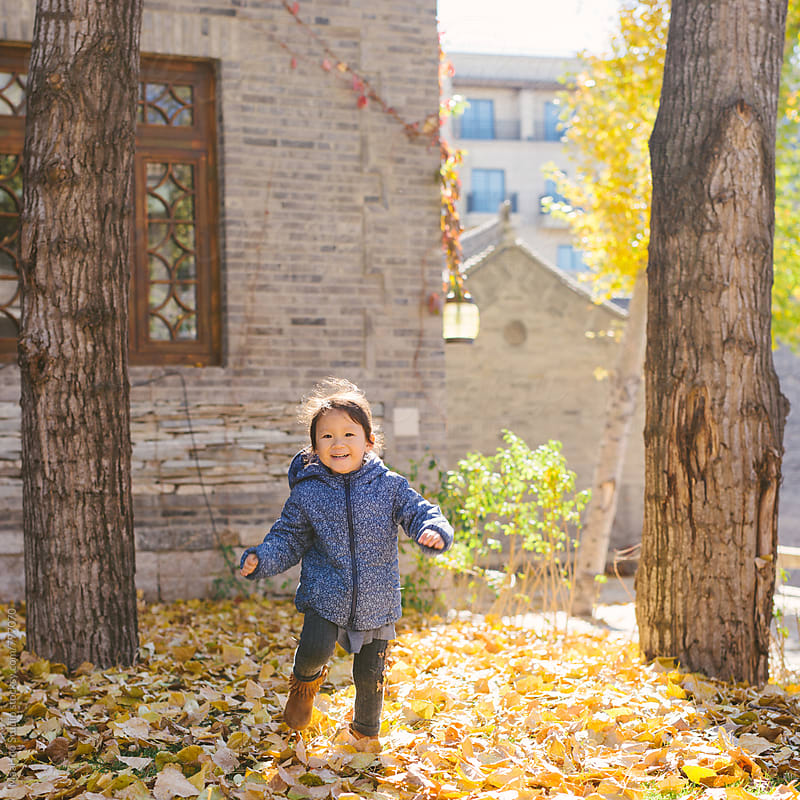 Cheerful toddler girl running in a park on a sunny autumn day by MaaHoo Studio for Stocksy United