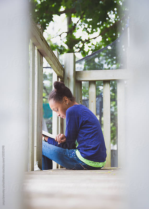 Preteen girl reading a book while sitting on the top of a outdoor playset by anya brewley schultheiss for Stocksy United