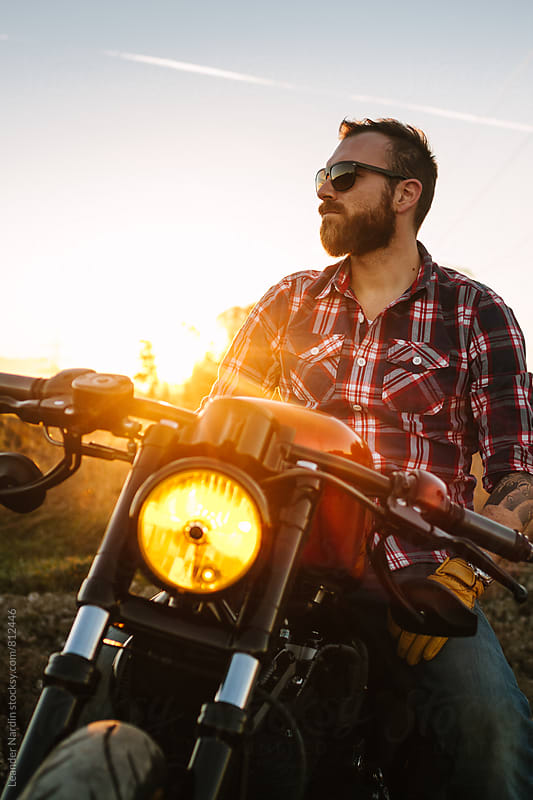 wild, young and free - casual bearded biker with sunglasses sitting on his bike enjoying the sunset by Leander Nardin for Stocksy United