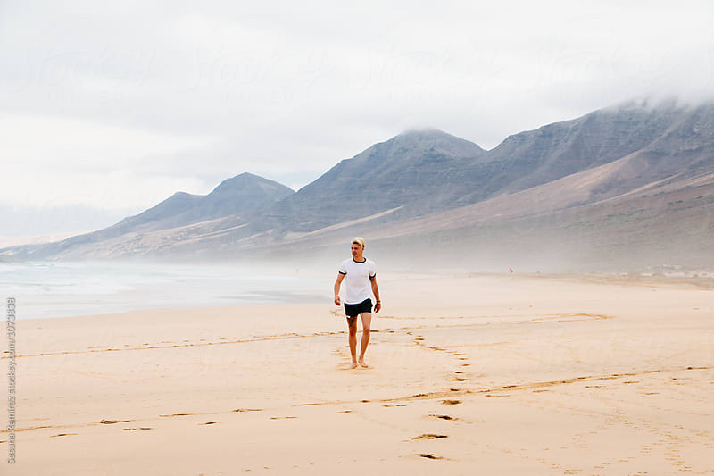 Young man walking along a beach paradise by Susana Ramírez for Stocksy United