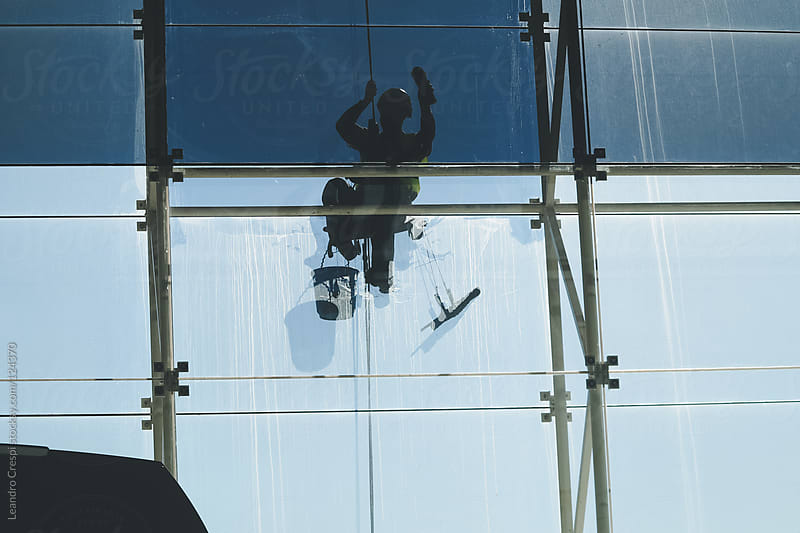Window cleaner doing maintenance labors by Leandro Crespi for Stocksy United