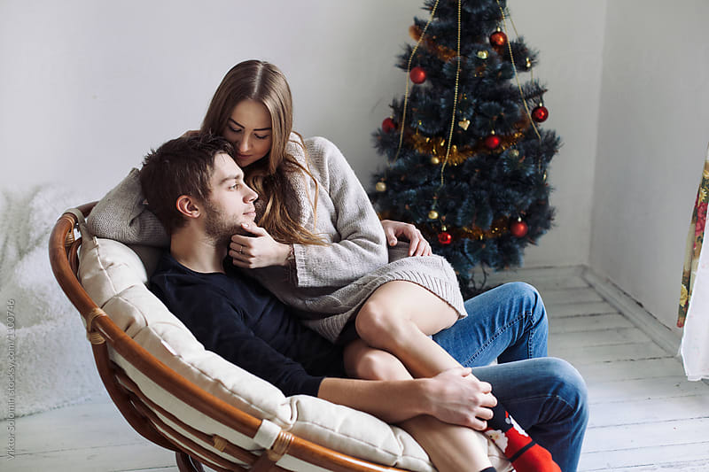 Christmas winter portrait of sensual couple sitting together   by Viktor Solomin for Stocksy United
