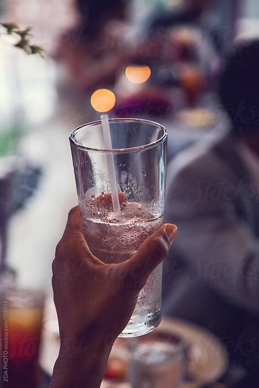 Brown-skinned woman holding a glass of water by ZOA PHOTO for Stocksy United