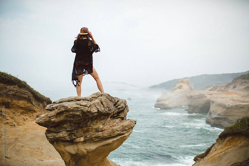 Young hip woman explores the Oregon Coast on a foggy day. by Kate Daigneault for Stocksy United