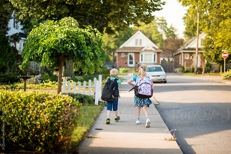Boy and Girl Walking Down Street To School In Autumn by JP Danko for Stocksy United