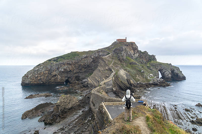 Hiker photographer looking at amazing island in Gaztelugatxe by ACALU Studio for Stocksy United