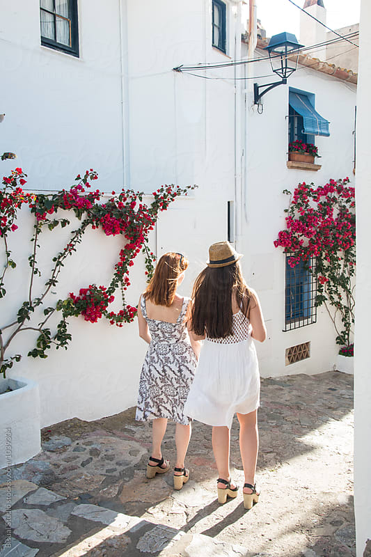 Two girlfriends walking on a mediterranean village by Bisual Studio for Stocksy United