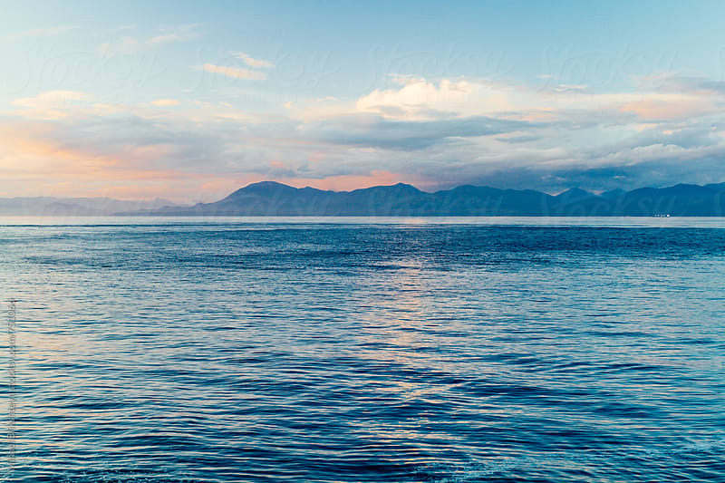 Scenic sunset over a strait with mountains in the background by Mihael Blikshteyn for Stocksy United
