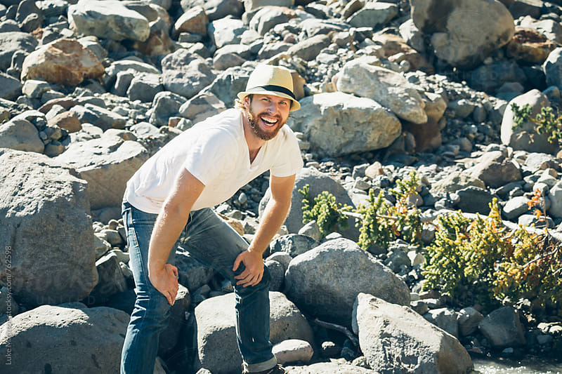 Bearded Blond Man Wearing Fedora And Smiling In Rocky Riverbed by Luke Mattson for Stocksy United