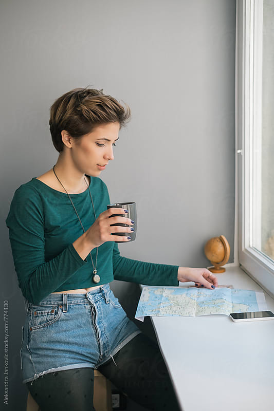 Young Woman Drinking Coffee and Looking at the Map by Aleksandra Jankovic for Stocksy United