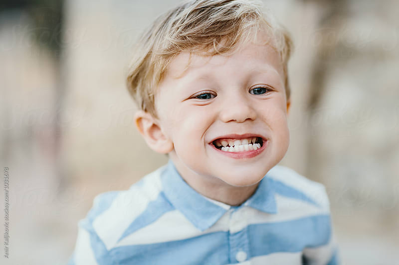Cute little boy grinning and showing his teeth by Amir Kaljikovic for Stocksy United