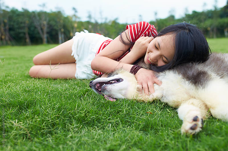 Happy young woman stroke her dog by Bo Bo for Stocksy United