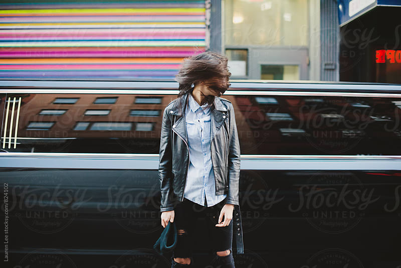 Free spirited girl standing in front of limousine by Lauren Naefe for Stocksy United