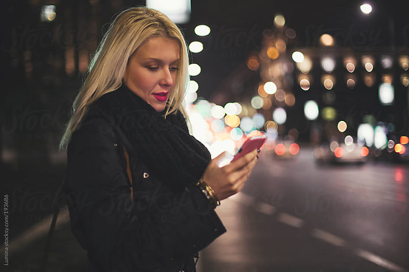 Woman Texting on the Street at Night by Lumina for Stocksy United