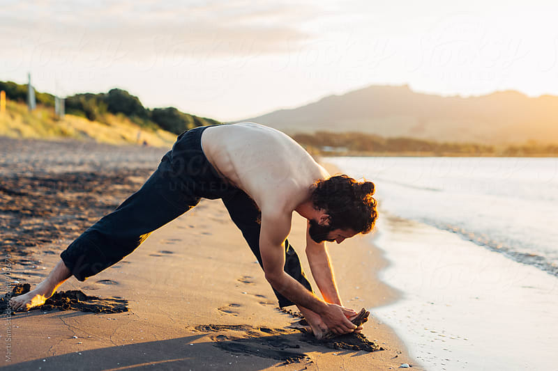 Man stretching on beach by Martí Sans for Stocksy United