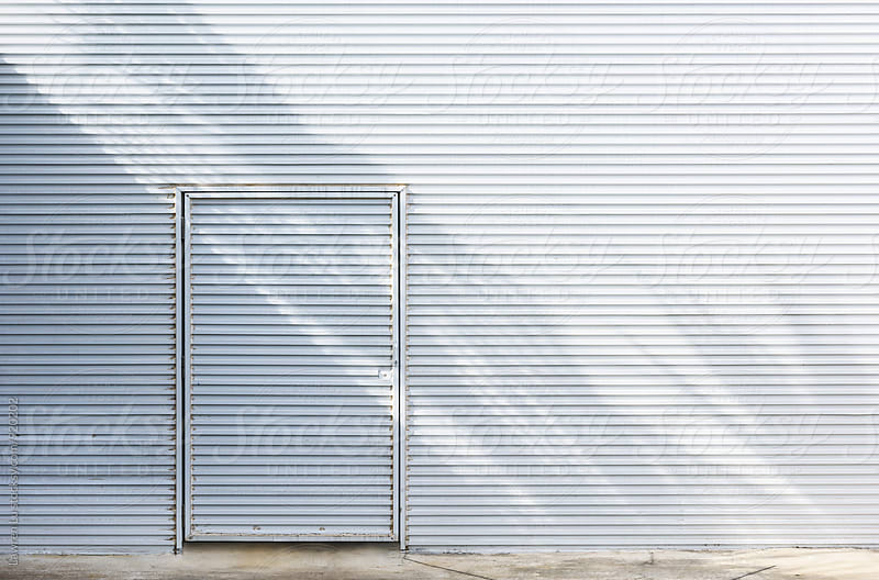 White metal siding wall with shadow and door by Lawren Lu for Stocksy United