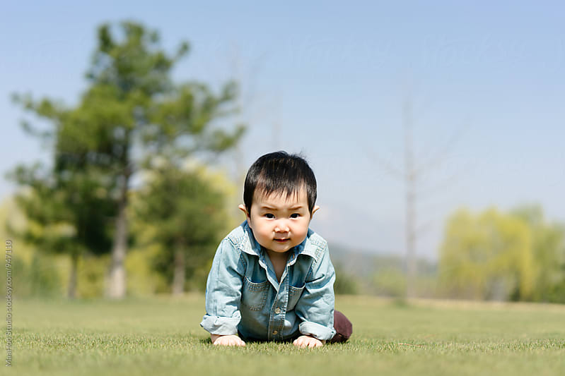 Baby boy crawling on grass in a garden by Maa Hoo for Stocksy United