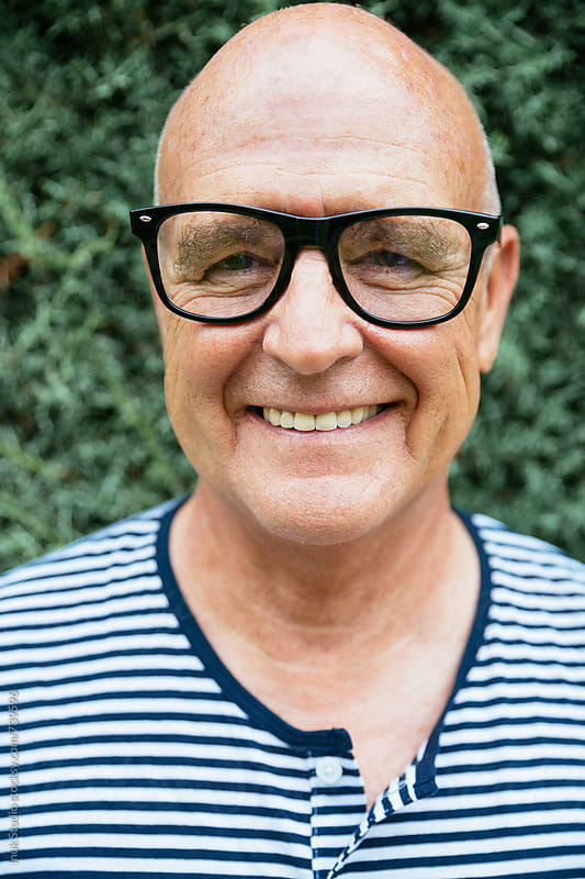Stylish bald senior man portrait smiling, wearing glasses and a marine stripe tshirt looking at the camera. by Inuk Studio for Stocksy United