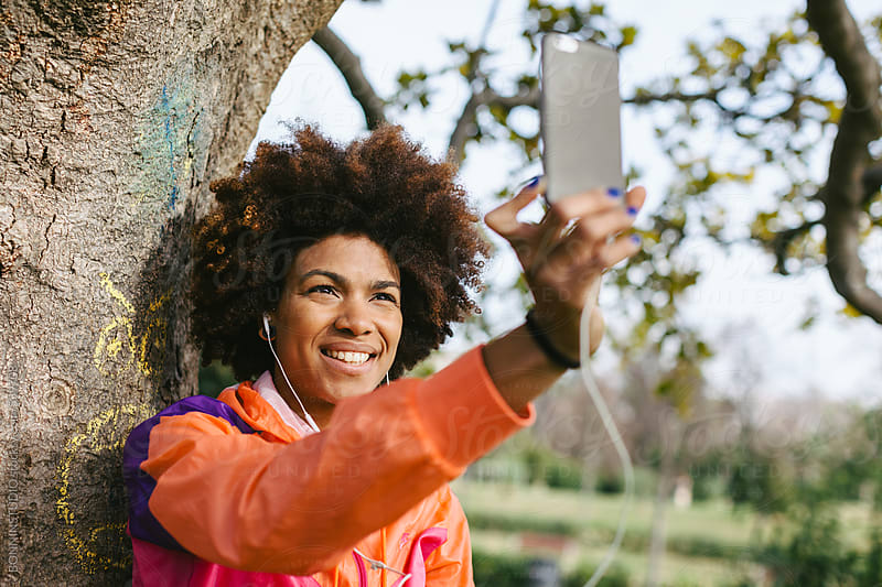 Young african american woman taking a selfie in the park. by BONNINSTUDIO for Stocksy United