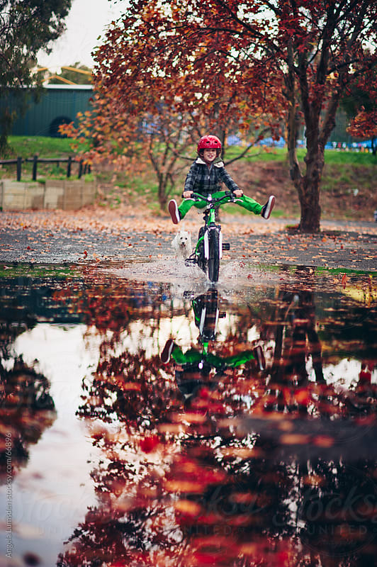 Boy riding a bike in a large puddle  by Angela Lumsden for Stocksy United