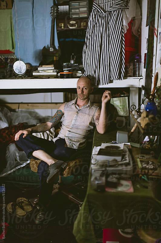 A tattooed artist in his ramshackle home. by Rachel Bellinsky for Stocksy United