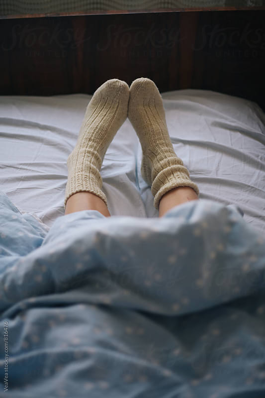 Female legs in cosy winter socks under the sheet by VeaVea for Stocksy United