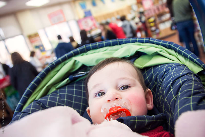 Baby in a grocery store by Holly Clark for Stocksy United