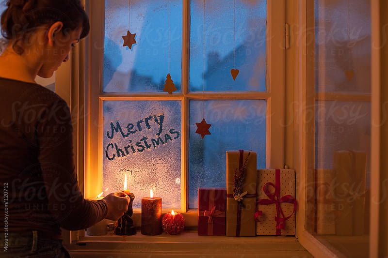 Woman Lighting Christmas Candles by Mosuno for Stocksy United