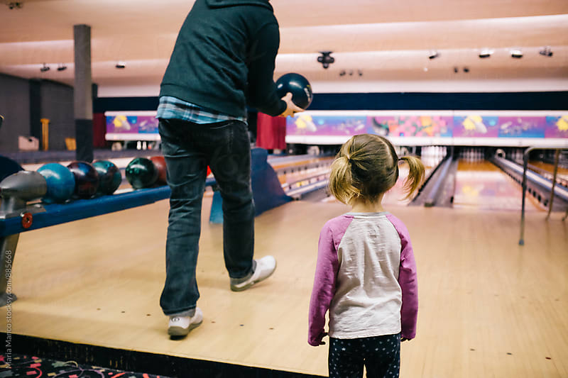 little girl watches man bowling by Maria Manco for Stocksy United