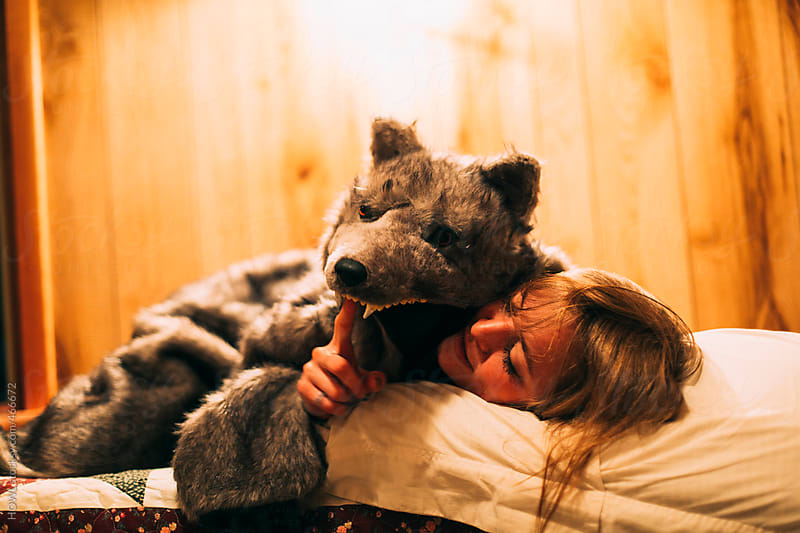 a drunk young woman in a wolf costume  by HOWL for Stocksy United