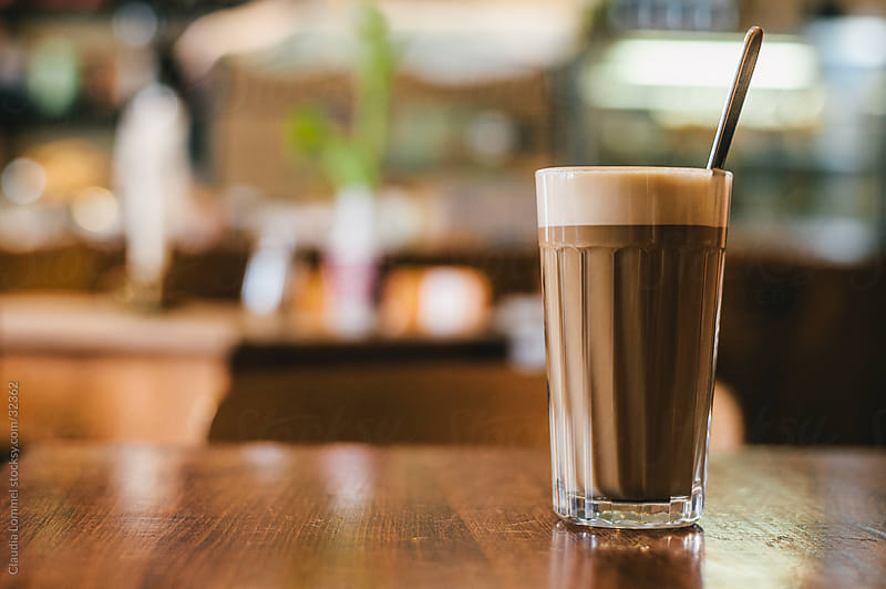 Lifestyle Shot of a Glass of Latte Macchiato, a White Coffee in a Coffee Bar by Claudia Lommel for Stocksy United