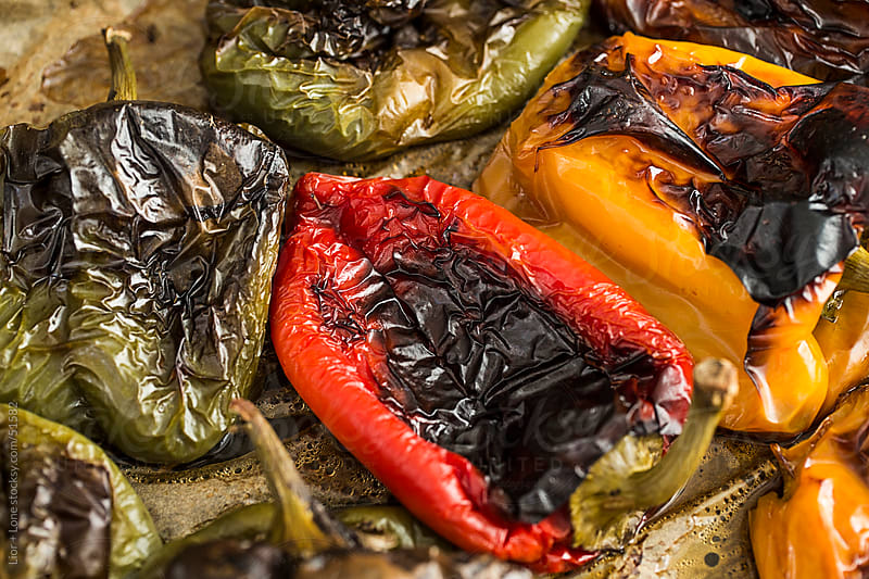 closeup of red, green, and yellow roasted bell peppers by Lior + Lone for Stocksy United