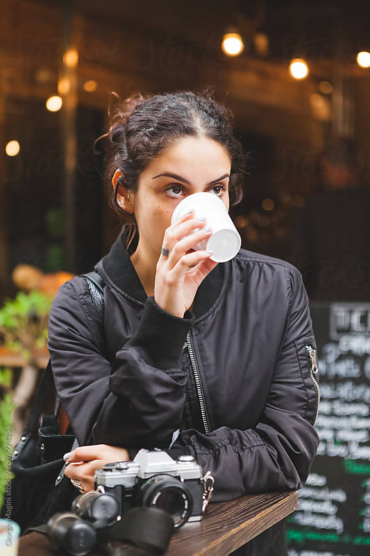 Thoughtful Female Photographer Having a Coffee Outdoors by Giorgio Magini for Stocksy United