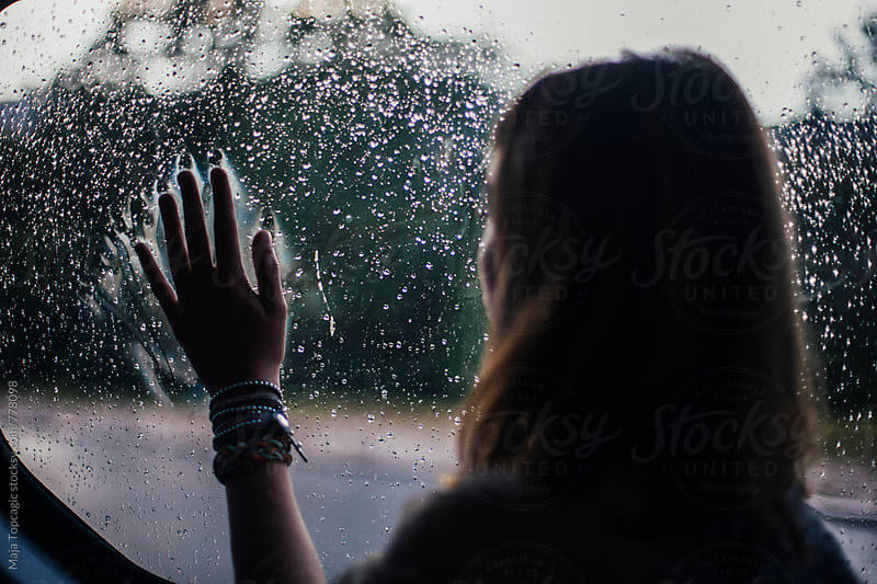 Young beautiful woman looking through the window while driving in the car by Maja Topcagic for Stocksy United