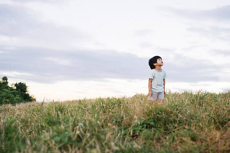 A boy looking up to the sky at a field by Alita Ong for Stocksy United