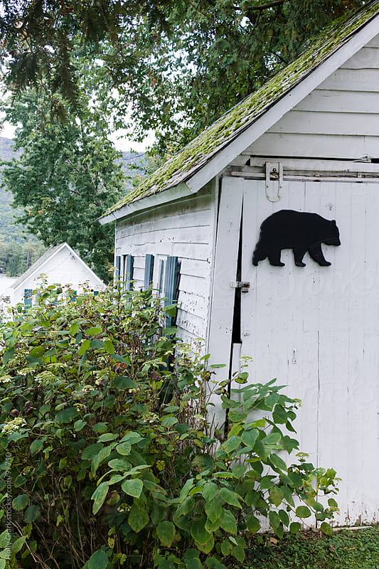 An old barn with moss on its roof and a bear decoration on its d by Holly Clark for Stocksy United