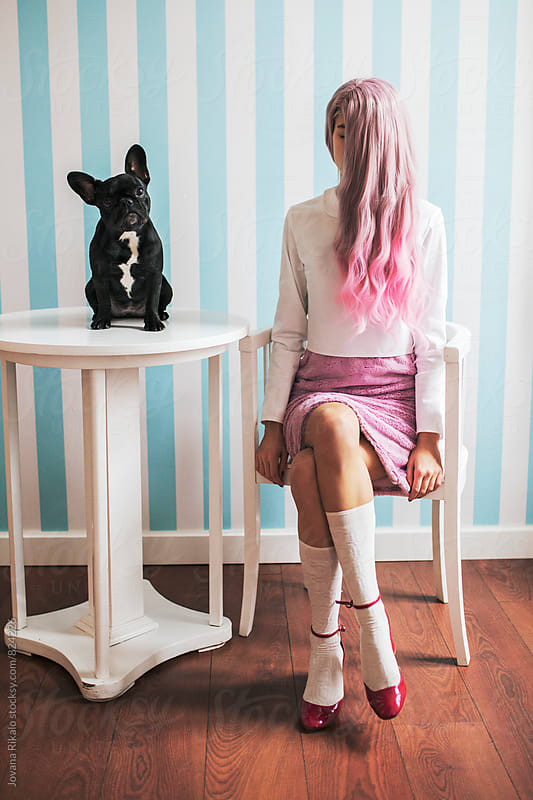 Fashionable young woman sitting on a chair; french bulldog sitting on a table by Jovana Rikalo for Stocksy United