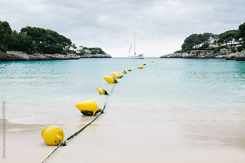Buoys leading out to a yacht by Darren Seamark for Stocksy United