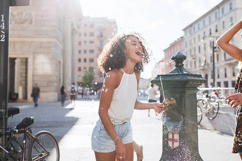 Girl having fun with the water of a fountain on a hot day by michela ravasio for Stocksy United